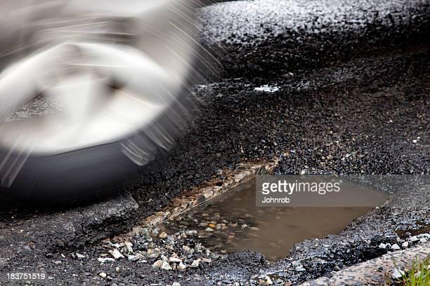 Moving auto tire about to enter large pothole, Motion blur