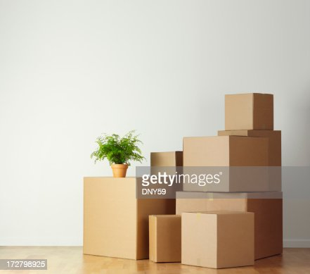 Moving boxes stacked in an empty room ready for movers
