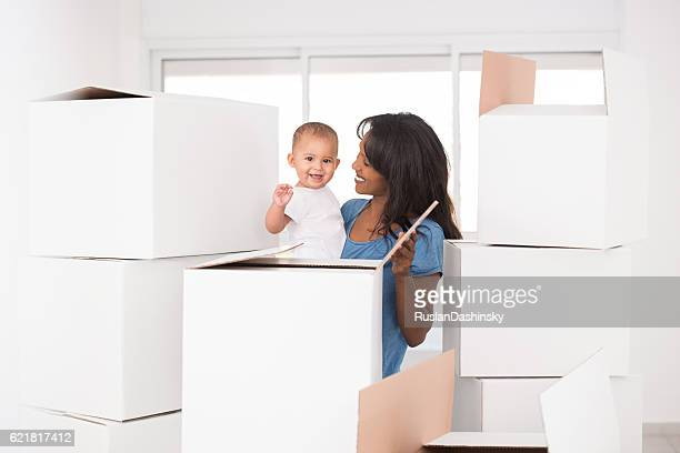 Moving day. Mother and baby unpacking.