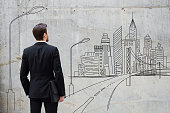 Rear view of young businessman standing against concrete wall with city sketch on it