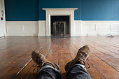 Sitting on bare floorboards in an empty, old, Georgian room. Waiting for the furniture and thinking about interior decoration. POLV shot including the photographer's legs.