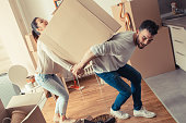 Young couple carrying big cardboard box at new home.Moving house.