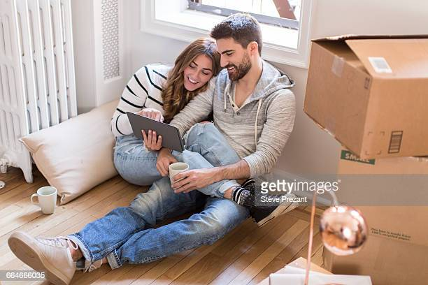 Moving house: Young couple sitting in room full of boxes, looking at digital tablet