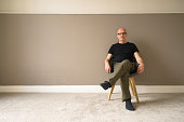 Mature man moving in to a new home sits on a chair in an empty room; walls painted, new carpet, ready for the furniture.