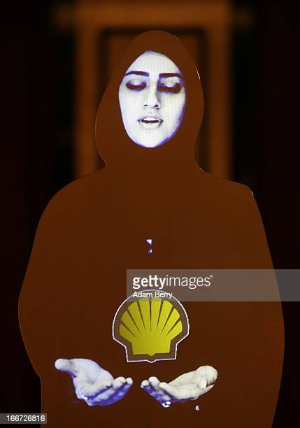 A moving video image of a woman holding the Royal Dutch Shell logo is projected at the Qatar Business and Investment Forum 2013 on April 16 2013 in...