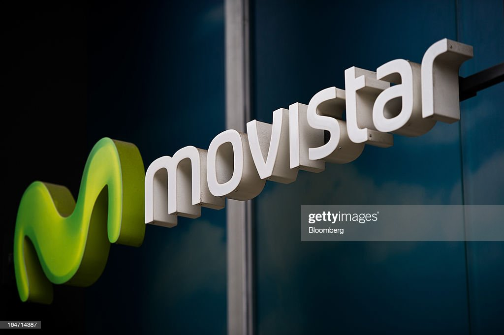A Movistar logo sits on display outside a Telefonica SA phone store in Barcelona, Spain, on Tuesday, March 26, 2013. Telefonica, seeking to reduce net debt by more than 4 billion euros this year, is following companies such as Repsol SA, Spain's biggest oil company, and builder Actividades de Construccion & Servicios SA, to sell treasury shares. Photographer: David Ramos/Bloomberg via Getty Images