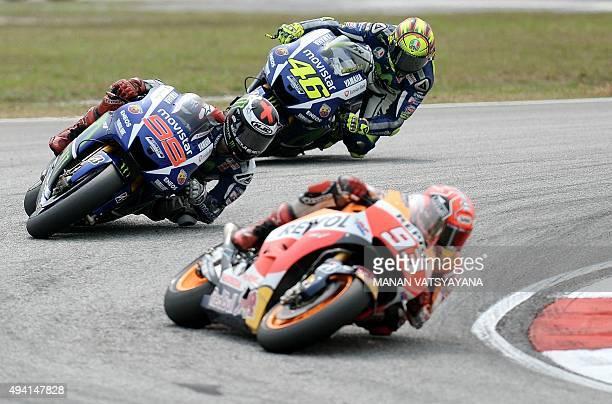 Movistar Yamaha MotoGP's Italian rider Valentino Rossi and Spanish rider Jorge Lorenzo chase Repsol Honda Team's Spanish rider Marc Marquez during...