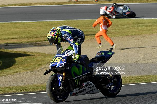 Movistar Yamaha MotoGP's Italian rider Valentino Rossi mounts his motorcycle moments after recovering from his crash at the hairpin curve during the...