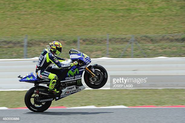 Movistar Yamaha MotoGP's Italian rider Valentino Rossi performs a wheelie as as he takes part in the second Moto GP free practice of the Catalunya...