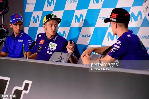 Movistar Yamaha MotoGP's Italian rider Valentino Rossi speaks with Movistar Yamaha MotoGP's Spanish rider Maverick Vinales beside Team Suzuki...