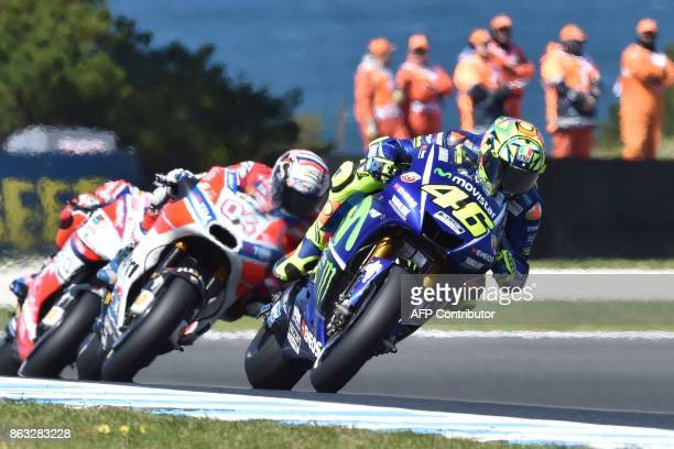 Movistar Yamaha rider Valentino Rossi of Italy powers ahead of compatriot Ducati rider Andrea Dovizioso during the first practice session of the...
