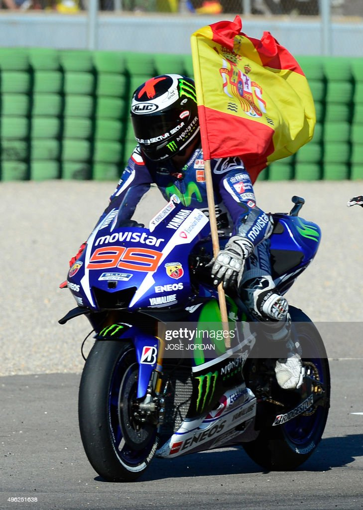 Movistar Yamaha's Spanish rider Jorge Lorenzo rides with a Spanish flag after winning the race and the 2015 MotoGP world championship tiltle after the MotoGP motorcycling race at the Valencia Grand Prix at Ricardo Tormo racetrack in Cheste, near Valencia on November 8, 2015. AFP PHOTO/ JOSE JORDAN