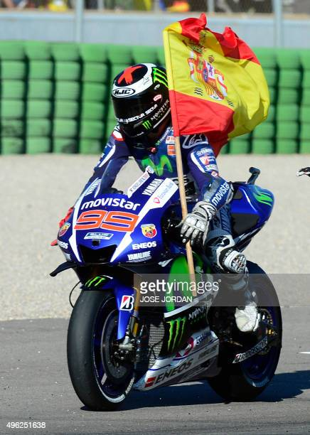 Movistar Yamaha's Spanish rider Jorge Lorenzo rides with a Spanish flag after winning the race and the 2015 MotoGP world championship tiltle after...