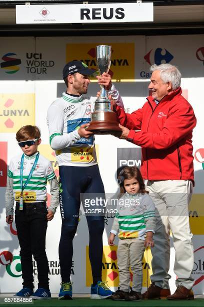 Movistar's Spanish rider Alejandro Valverde is handovered the trophy as he celebrates his overall leader jersey on the podium on the sixth day of the...