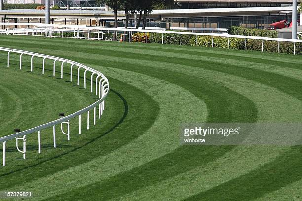 Mowed lawn used as a horse racing track restricted by fence