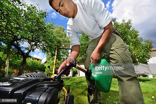 Mowing the lawn in nice green garden. Refuelling green petrol