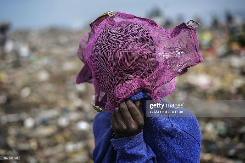 A Mozambican boy covers his face as others sift through garbage at the Maputo municipal garbage dumping site in Maputo on October 14 2014...