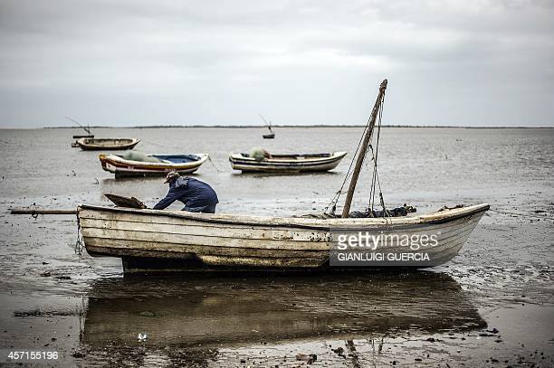 A Mozambican fisherman works on his boat during a low tide at Costa do Sol fishemen village in Maputo Mozambique on October 13 2014 Mozambicans will...