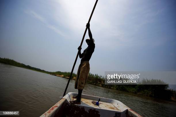 A mozambican man pushes a boat on a small river to cross to the Vinho village on November 6 2010 in the Gorongosa National Park Mozambique Gorongosa...