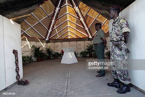Mozambican soldiers stand guard 22 June 2005 in Maputo at the entrance of a simple starshaped monument marking the graves of 26 liberationera heroes...