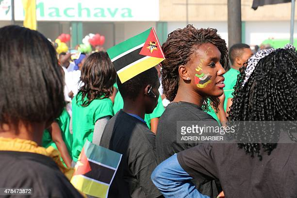 Mozambican youth celebrate with Mozambican national flags one painted on a teenager's face during the celebrations for the 40th anniversary of...
