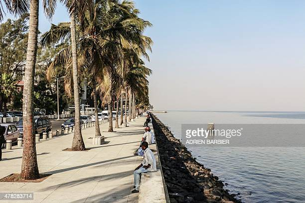 Mozambicans sit on a newly built promenade at the riviera in Maputo on the eve of the 40th anniversary of Mozambique's independence from Portugal on...