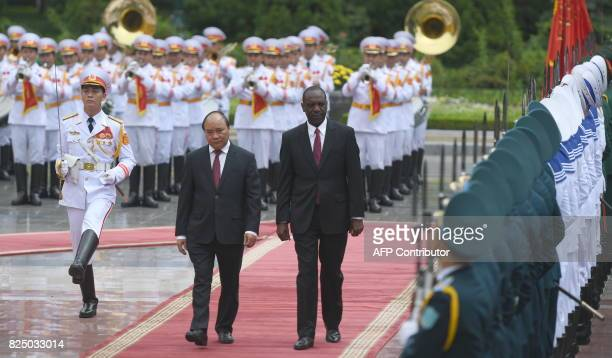 Mozambique's Prime Minister Carlos Agostinho do Roserio and his Vietnamese counterpart Nguyen Xuan Phuc review an honour guard during a welcoming...