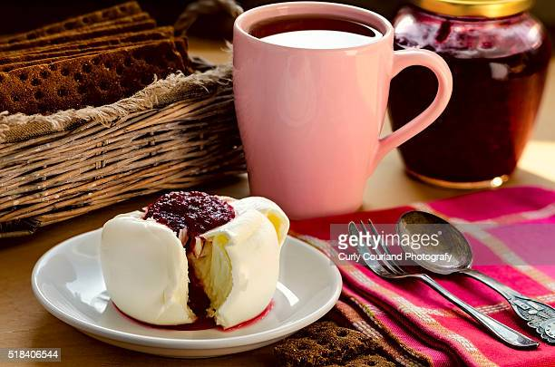 Mozzarella cheese with cranberry sauce, tea into the pink cup and wholegrain crisps, jar with cranberry jam, vintage silver spoon and dessert fork, checkered cloth