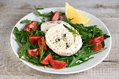 Mozzarella salad with arugula, cherry tomatoes, lemon, seasoned with spices and olive oil