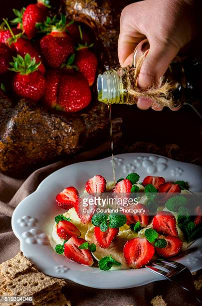 Mozzarella, strawberry and mint salad with woman hand pouring olive oil