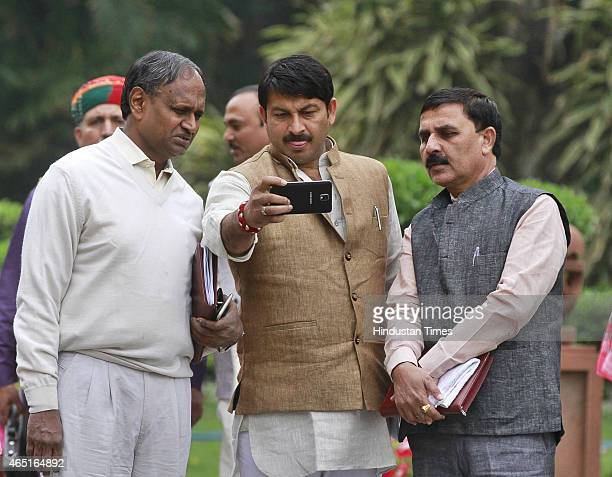 MPs Manoj Tiwari and Udit Raj looking at mobile phone after the BJP Parliamentary Board meeting during budget session at Parliament house on March 3...