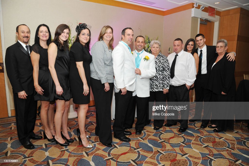 Mr. and Mr. Joey and Dennis Adisano-Sessa pose with guests at a wedding for 11 couples at the Crowne Plaza Times Square on November 11, 2011 in New York City.