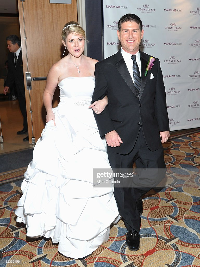 Mr. and Mrs. Aaron (R) and Sabrina Greenwald pose at a wedding for 11 couples at the Crowne Plaza Times Square on November 11, 2011 in New York City.