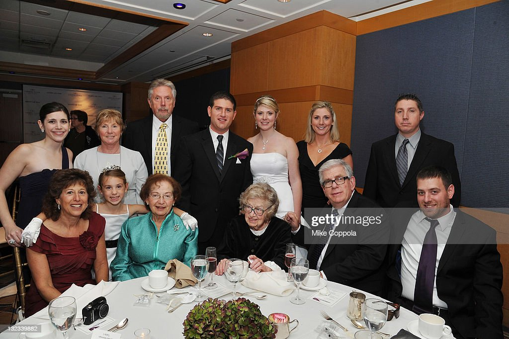 Mr. and Mrs. Aaron and Sabrina Greenwald (C) pose with guests at a wedding for 11 couples at the Crowne Plaza Times Square on November 11, 2011 in New York City.