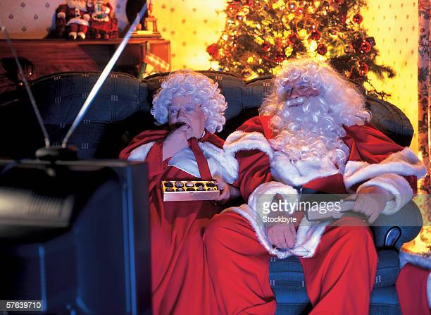 Mr.. and Mrs.. Claus watching television on the couch