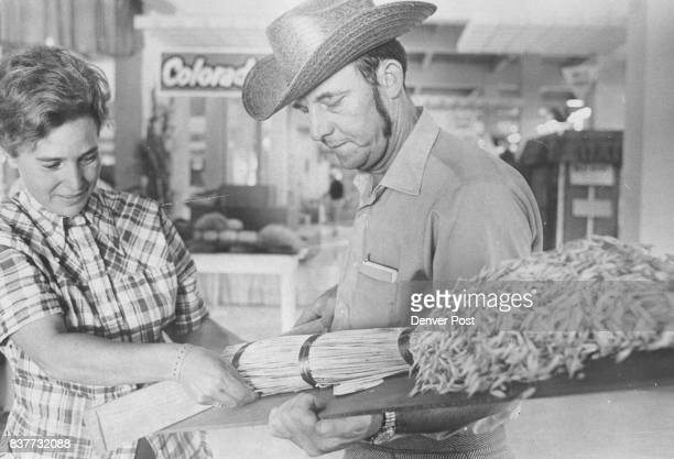 Mr and Mrs Everett Duncan of Sterling Colo display a Sheaf of Oats from Logan County Only about a dozen Colorado counties were entered in sheaf grain...