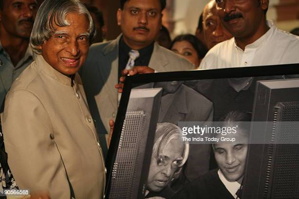 Mr APJ Abdul Kalam president of India looks at his own picture during India Today photographer Sipra Das's photo exhibition at the president house...