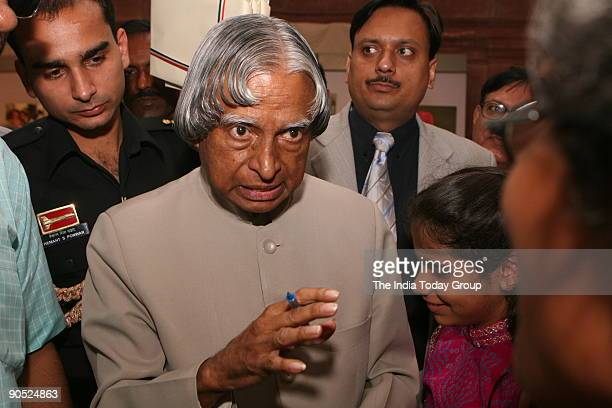 Mr APJ Abdul Kalam president of India signs an autograph during India Today photographer Sipra Das's photo exhibition at the president house New Delhi