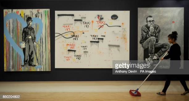 Mr Brainwash's Chaplain 2011 Taki's Untitled 2009 and Jef Aerosol's Keith Haring 2012 are displayed as gallery assistant Jacqueline Sevcik sweeps the...