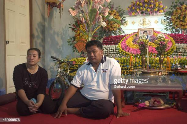 Mr Chamnan Boonmanuch and Mrs Chongrak Boonmanuch sit in front of a coffin containing the body of their son Tae the 6 year old boy who was the first...
