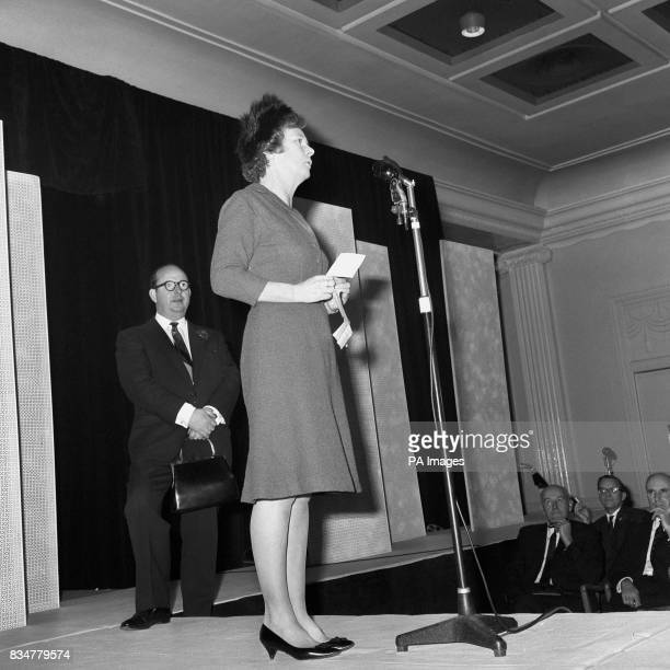 Mr Edward Rayne President of the British Footwear Manufacturers' Federation stands in the back ground holding Mrs Harold Wilson's handbag as the...