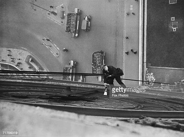 Mr Larkin lowers himself from a rope to clean the face of Big Ben the famous clock on the Houses of Parliament 4th March 1930