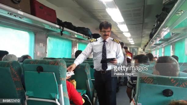 HARIDWAR UTTARAKHNAD INDIA SEPTEMBER 15 Mr Ramesh Kumar Assistant Superintendent on the Shatabadi Express a high speed train using a mobile tablet to...