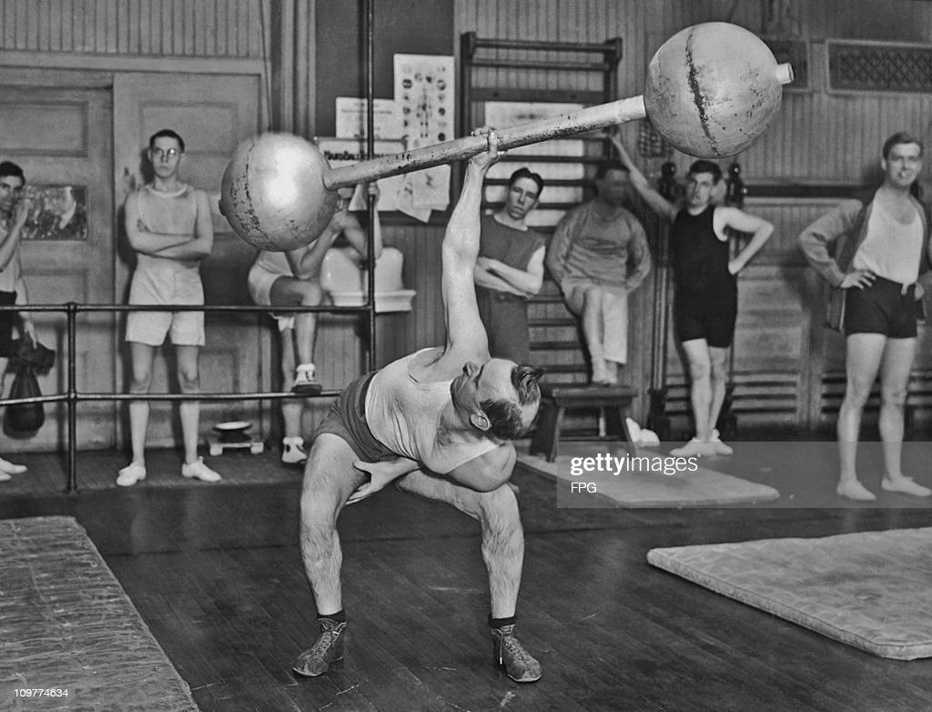Mr Smith of the West Side YMCA in New York breaking the record for a one handed lift circa 1930. The dumbbell weighs 225 lbs.