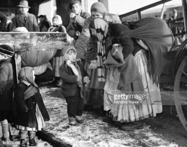 Mère de famille gitane donnant une pipe à fumer à son enfant pour le tenir calme en attendand le train à Poppendorf Allemagne circa 1945