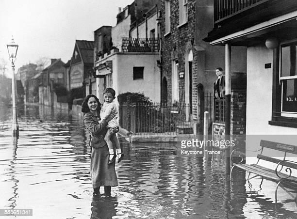 Mère et son enfant traversant une rue inondée dans le quartier de StrandontheGreen à Londres RoyaumeUni le 2 novembre 1936