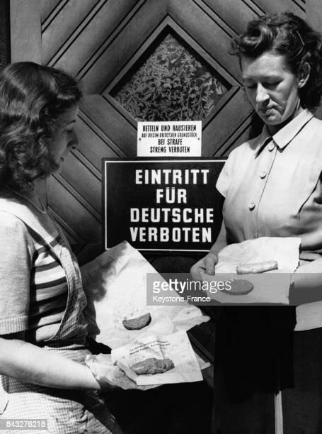 Mères de familles anglaises présentant les rations pour les petits déjeuners une saucisse et trois morceaux de viande pour quatre personnes et pour...