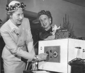 MAY 23 1956 Mrs Alma Schneider superintendent of the mint and Mrs Ralph Horst experiment with a worthless 'Ozone Generator' which sold for $500...