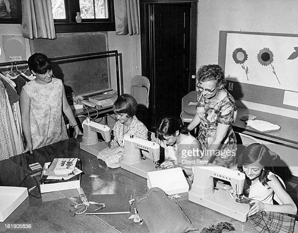 AUG 25 1967 AUG 30 1967 Mrs Aurelia Hill Right Instructs Girls In Intricacies Of Sewing Four of the girls in her classes are from left Patti Lally...