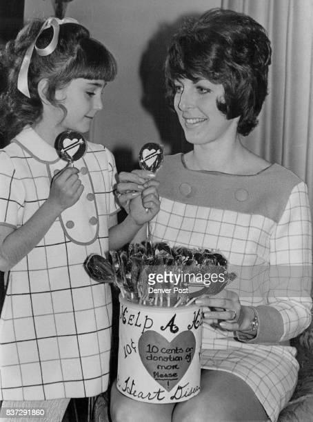 "Mrs Brent Clayton Alpha Phi alumnae member offer a heartshaped lollipop to Lisa Rhodes daughter of Dr and Mrs Edward Rhodes See ""Each Lollipop Helps""..."